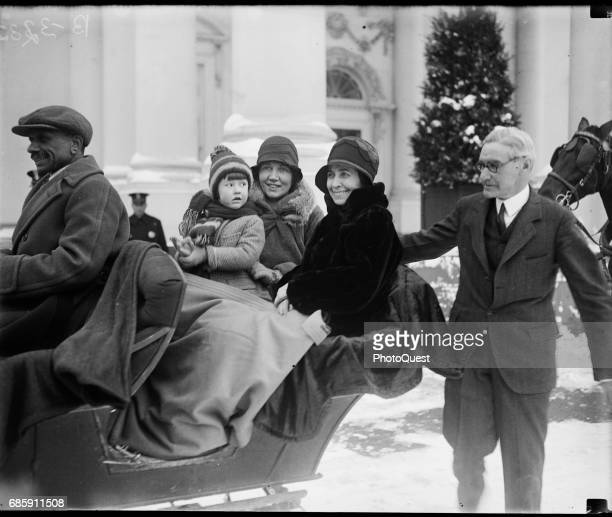 American First Lady Grace Coolidge smiles with unidentified others as she sits in a sleigh while Chief White House Usher Ike Hoover walks beside them...