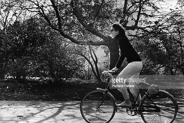 American first lady Jacqueline Kennedy Onassis rides a bicycle down a wooded path through Central Park New York New York November 8 1970