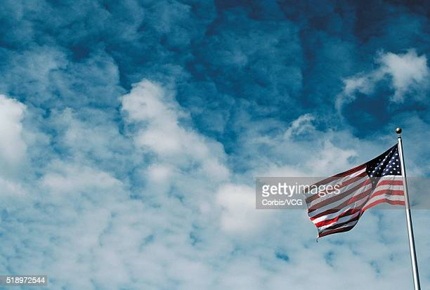 american flag against cloudy sky - vcg stock pictures, royalty-free photos & images