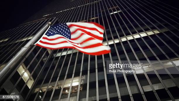 american flag along 34th street in midtown manhattan, at night. new york city, usa - flagpole sitting stock photos and pictures