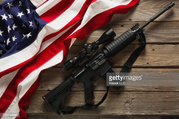 American flag and rifle against wooden wall