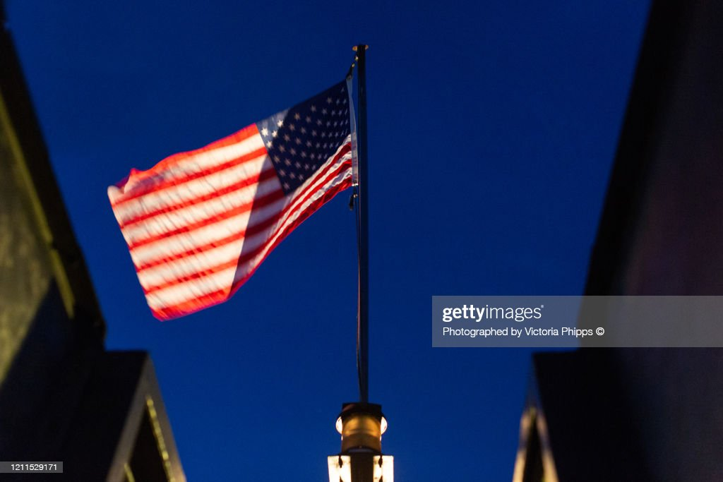 American flag blowing in the wind against a blue sky : Stock Photo