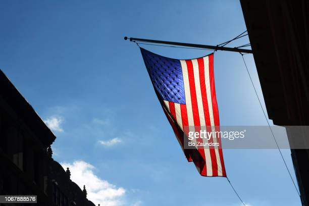 American flag, brightly lit by sunlight, against a blue sky, in NY.C