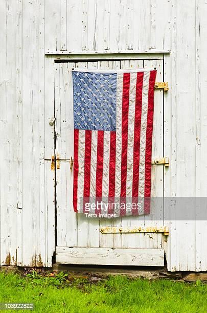 American flag draped on door of barn