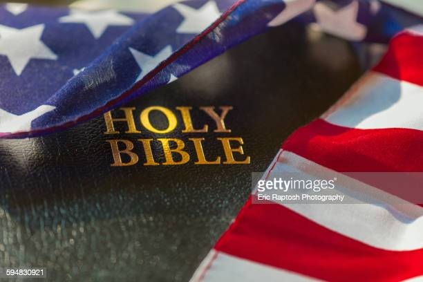 american flag draped over bible - conservative politics stock pictures, royalty-free photos & images
