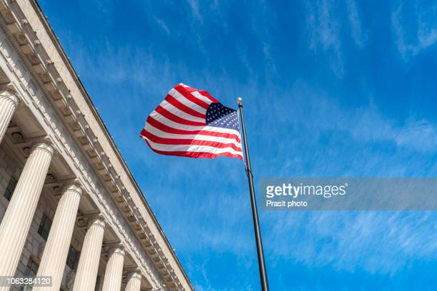 american flag flapping boldly in the wind with the supreme court in washington dc, usa. - constitution stock pictures, royalty-free photos & images