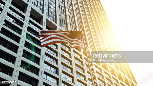 new york city, ny, usa - october 11, 2017: american flag flapping in front of corporate office building in lower manhattan - government stock pictures, royalty-free photos & images