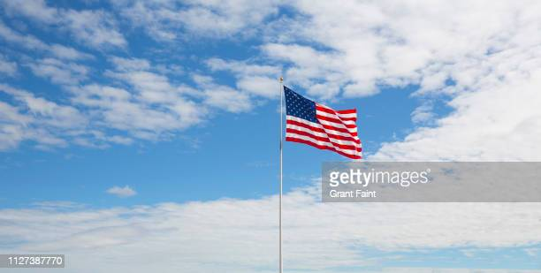 american flag flying in wind. - stars and stripes stock pictures, royalty-free photos & images