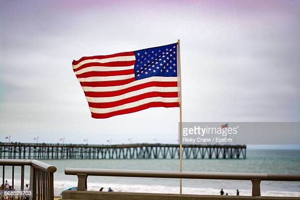 American Flag Flying On Beach Against Sky