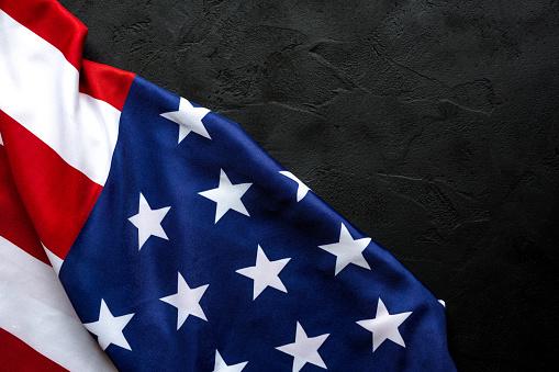American Flag freely lying on concrete black dark background 1250507347