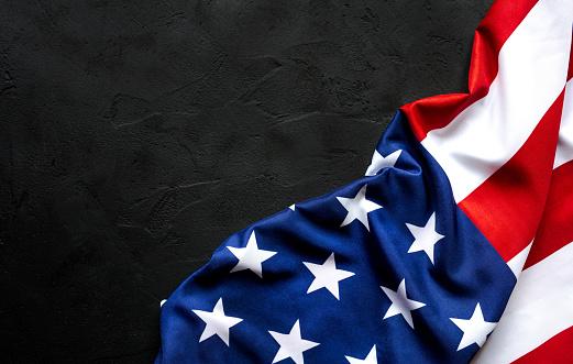 American Flag freely lying on concrete black dark background 1250508530