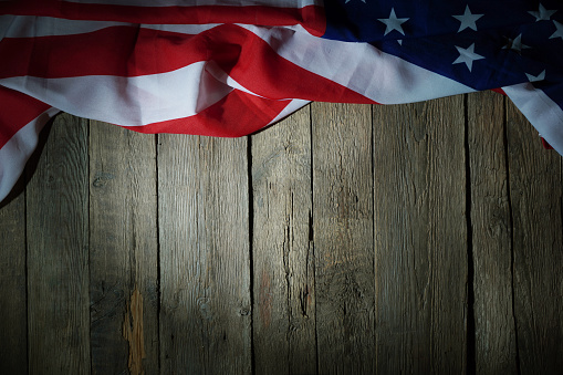 American flag freely lying on the textured wooden background. News template about the America. 1255022014