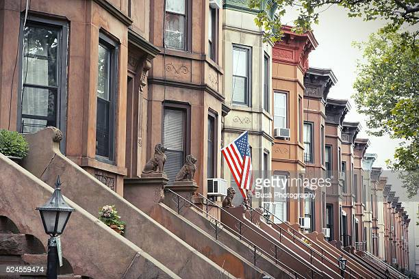 American flag hanging from the porch of a house in a residential district of Brooklyn, New York City