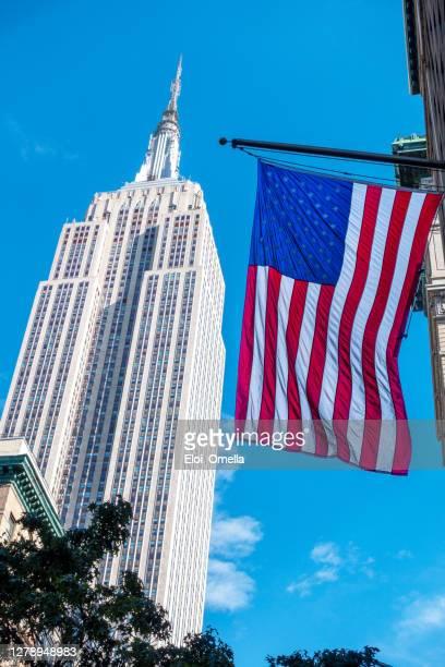 bandera estadounidense frente al edificio empire state en nueva york, ee.uu. - new york state fotografías e imágenes de stock