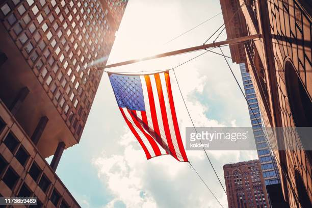 american flag in midtown manhattan - usa stock pictures, royalty-free photos & images