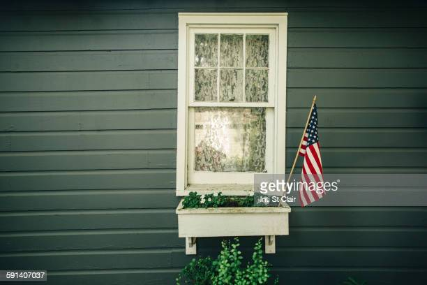 American flag in window box outside house