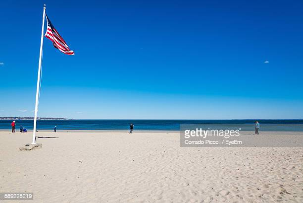 American Flag On Beach Against Clear Blue Sky
