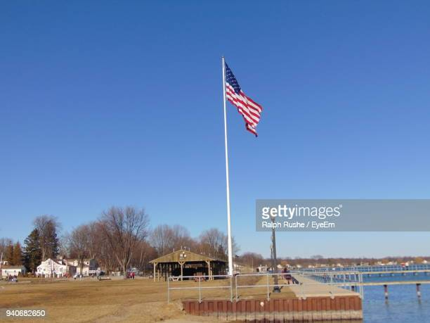 American Flag On Field Against Clear Blue Sky