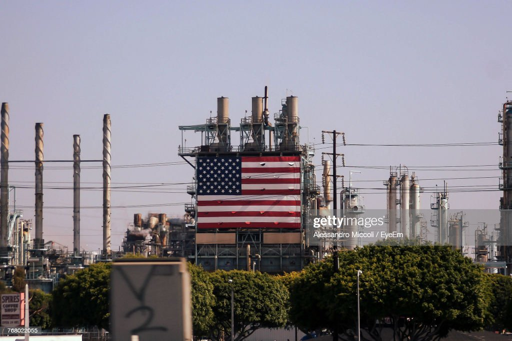 American Flag On Industry Building Against Clear Sky : Stock Photo