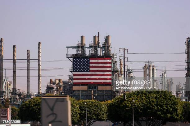american flag on industry building against clear sky - alessandro miccoli fotografías e imágenes de stock