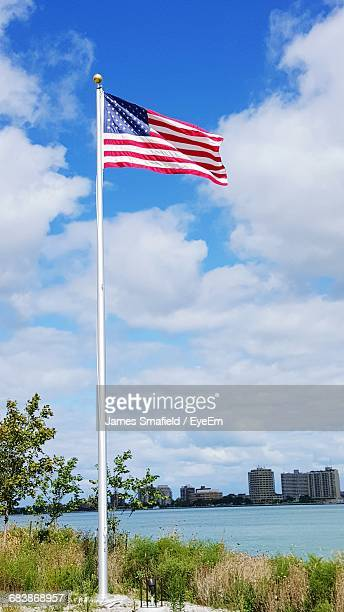 american flag on lakeshore against cloudy sky - ポートヒューロン ストックフォトと画像