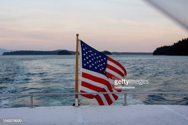american flag on the back of a boat, san juan islands, washington, united states - american flag ocean stock pictures, royalty-free photos & images