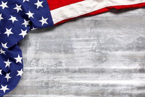 US American flag on worn white wooden background. For USA Memorial day, Veteran's day, Labor day, or 4th of July celebration. With blank space for text. 1269395259