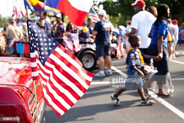 american flag, people in background preparing for parade. - parade stock pictures, royalty-free photos & images