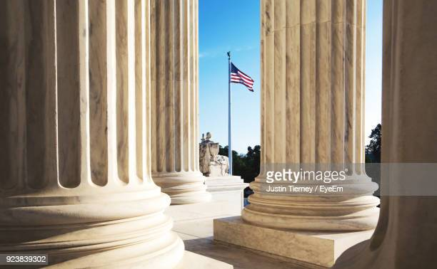american flag seen through columns - regierung stock-fotos und bilder