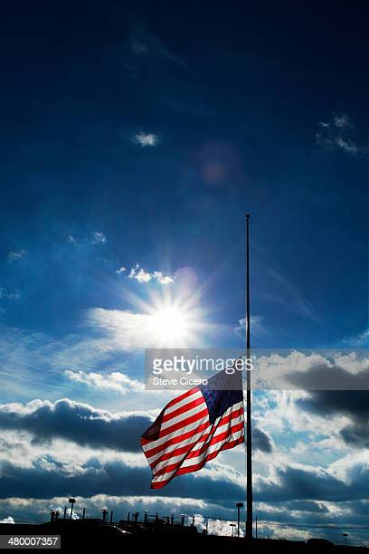 american flag silhoutted at half mast - half mast stock photos and pictures