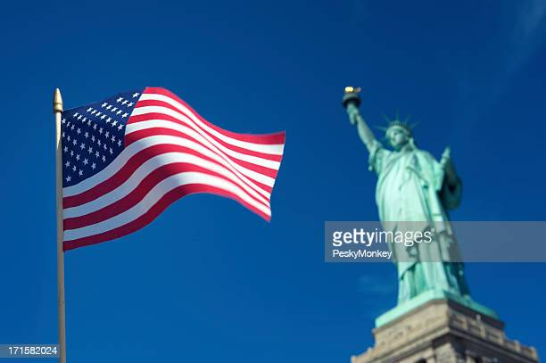 American Flag Waves at Statue of Liberty USA Blue Sky