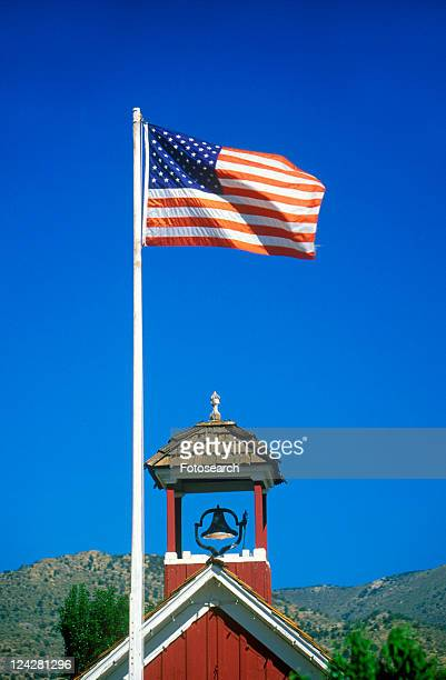 American flag waving above one room schoolhouse