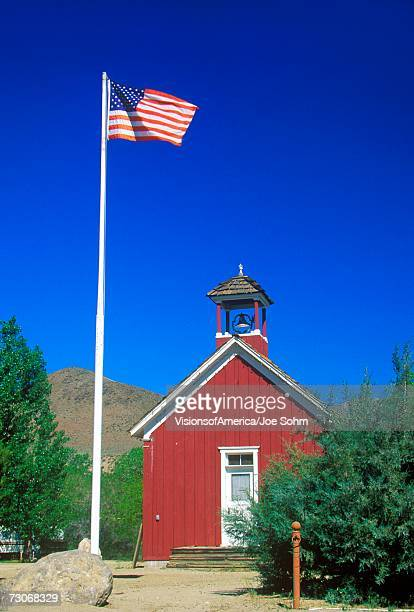 'American flag waving above one room schoolhouse, Wellington, NV'