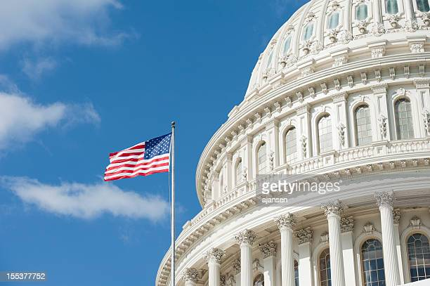 american flag waving in front of capitol hill - capitol hill stock pictures, royalty-free photos & images