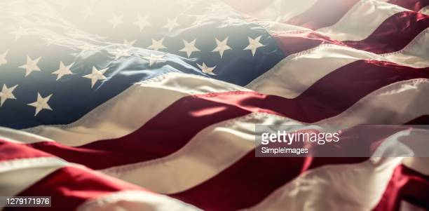american flag waving in the wind - american symbol of 4th of july independence day democracy and patriotism. - stars and stripes stock pictures, royalty-free photos & images