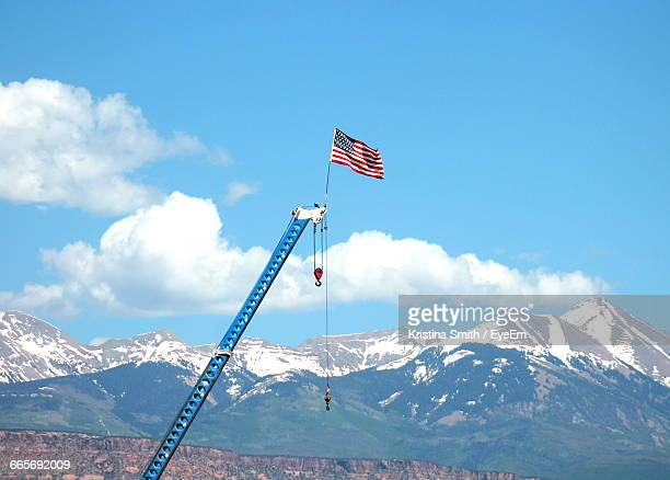 American Flag Waving On Crane Against Snowcapped Mountains