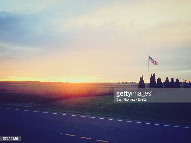 American Flag Waving On Grassy Field Against Sky