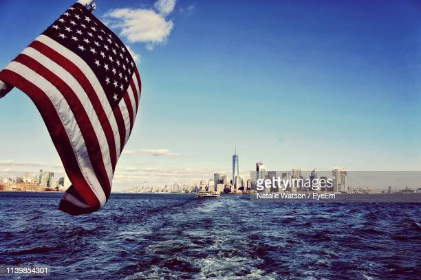 american flag waving over river with urban skyline in background - american flag ocean stock pictures, royalty-free photos & images