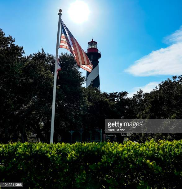 american flag with a lighthouse - st augustine lighthouse stock photos and pictures