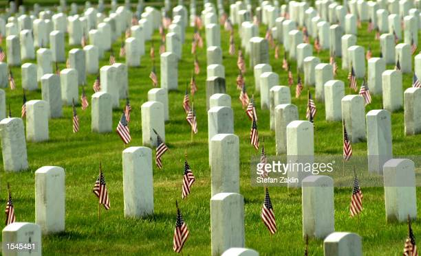 American flags adorn each grave in Arlington National Cemetary in honor of Memorial Day May 27 2002 in Arlington VA Thousands of tourists veterans...