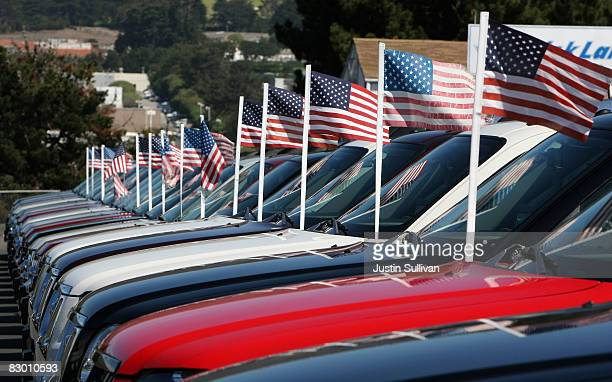 American flags are attached to the antennas of brand new Ford pickup trucks at a Ford dealership September 25 2008 in Colma California The Commerce...
