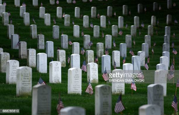 American flags are placed at graves at Arlington National Cemetery on May 25 2017 in Arlington Virginia in preparation for Memorial Day / AFP PHOTO /...