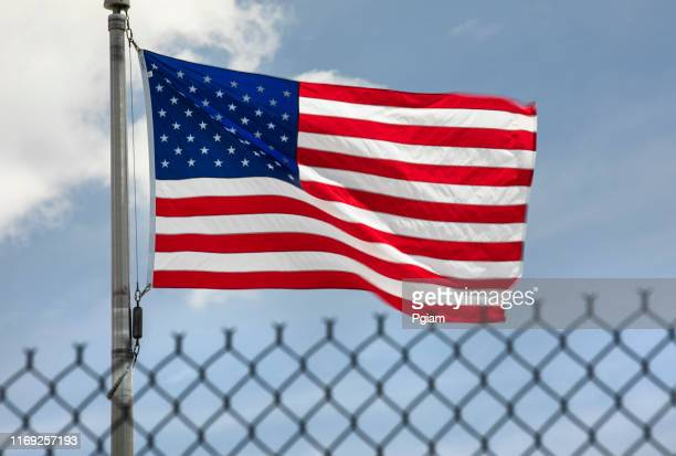 american flags blow in the wind behind an immigration security fence - illegal immigrant stock pictures, royalty-free photos & images