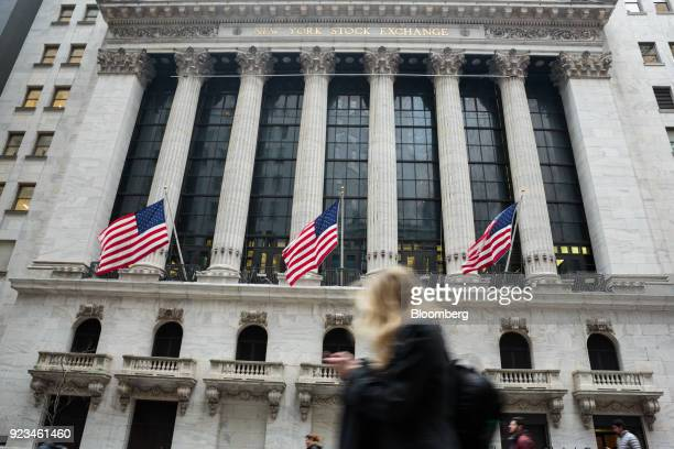American flags fly as a pedestrian walks past the New York Stock Exchange in New York US on Friday Feb 23 2018 US stocks rose with Treasuries and the...