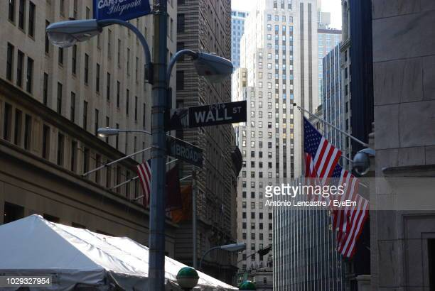 american flags on building at wall street - wall street lower manhattan stock pictures, royalty-free photos & images