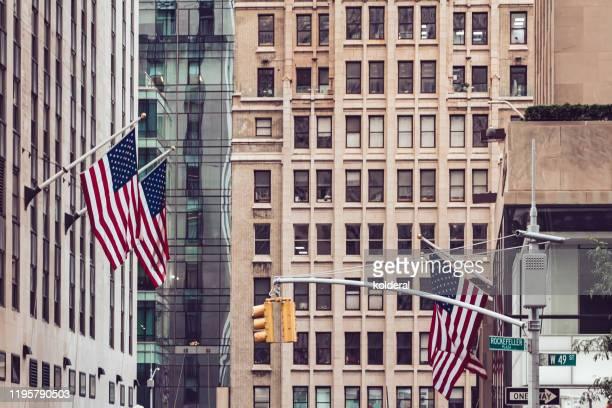 american flags on buildings in midtown manhattan - 五番街 ストックフォトと画像