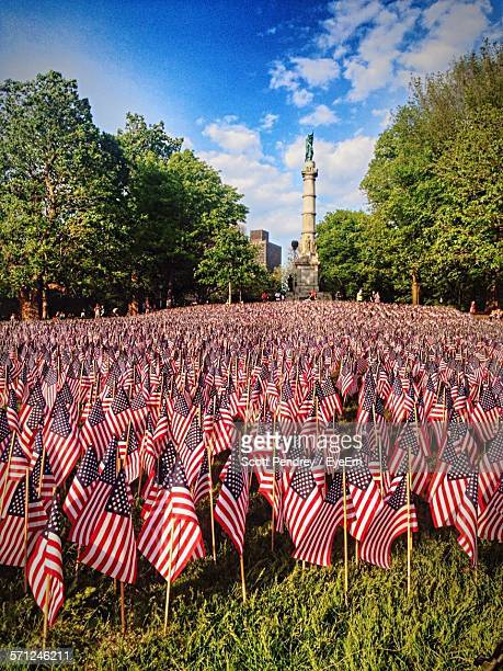 american flags on field by column against sky - memorial day remembrance stock pictures, royalty-free photos & images