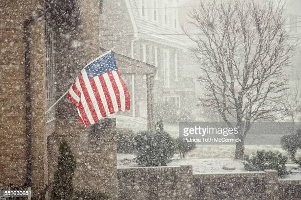 american flags on homes - snow squall stock photos and pictures
