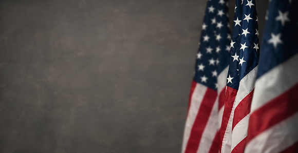 American flags over gray wal with copy space 1136801280