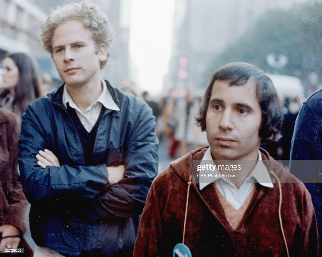 American folk and pop performers Art Garfunkel (left) and Paul Simon stand on a street during the filming of a televison special called 'Songs of America,' which aired on November 30, 1969.